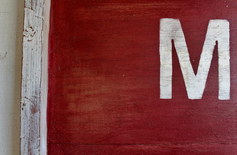 Letter M against red paint with white trim