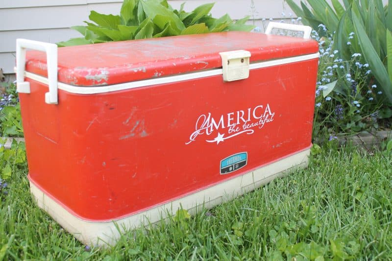 Large red cooler outside by flower bed