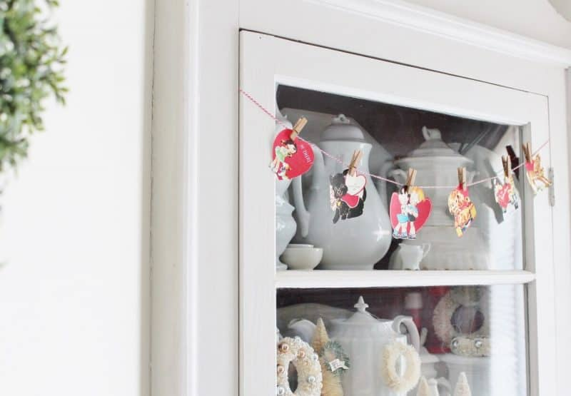 Side view of vintage valentine garland hanging from antique ironstone cupboard